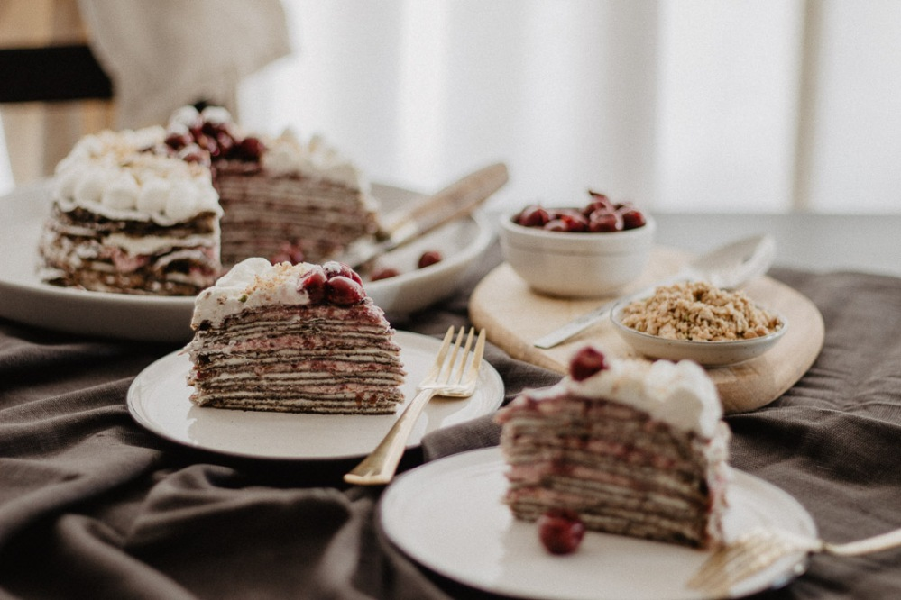 Tablesetting of Sliced Crepe Cake with Cherries, Nuts, and Goat Cheese